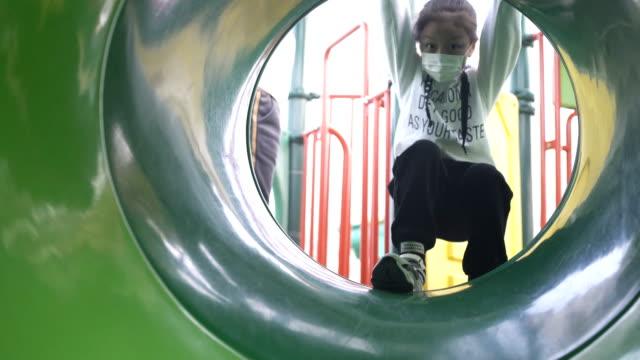 vídeos de stock e filmes b-roll de little girl playing in playground - parque infantil