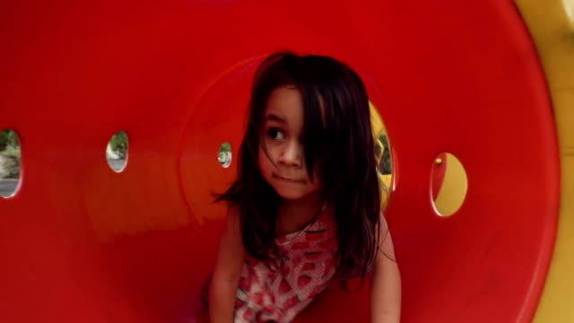 a little girl playing in red tunnel at playground - playground stock videos & royalty-free footage