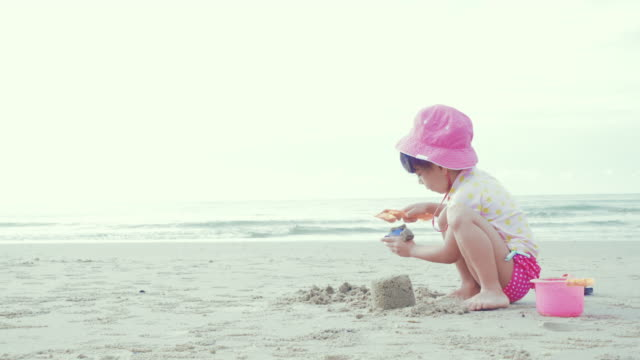 a little girl (6-7 years) playing in sand on beach - 6 7 years stock videos & royalty-free footage