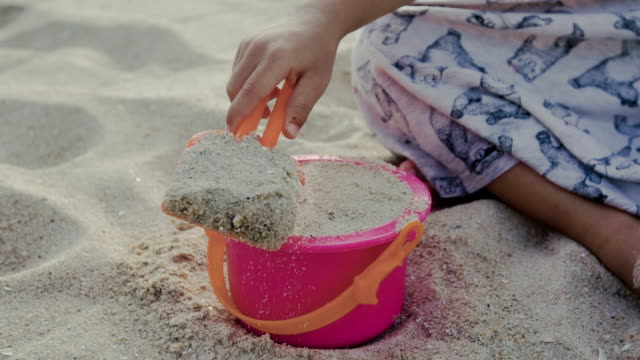 vídeos de stock e filmes b-roll de a little girl playing in sand with shovel and bucket on beach - balde