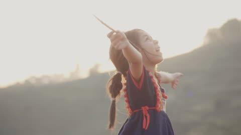 vidéos et rushes de petite fille jouant dans les champs - en l'air