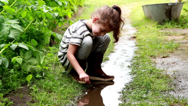 little girl playing in the puddle in the backyard - lawn stock videos & royalty-free footage