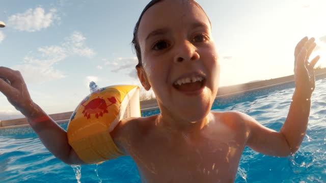 vídeos de stock, filmes e b-roll de menina brincando na piscina resort - acampamento de férias
