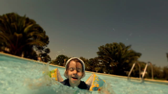little girl playing in the resort swimming pool - summer resort stock videos & royalty-free footage