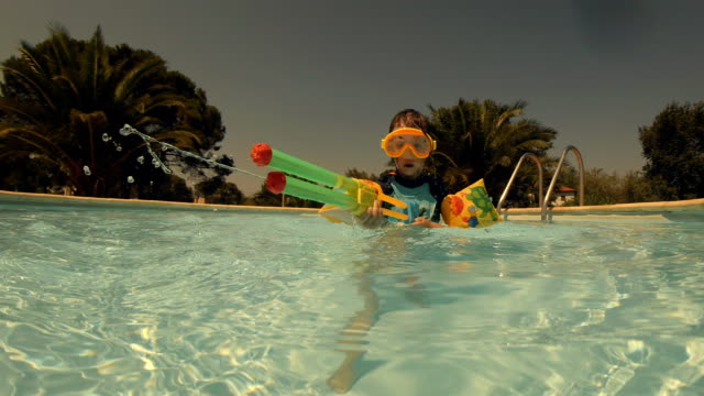 Little Girl Playing in The Resort Swimming Pool