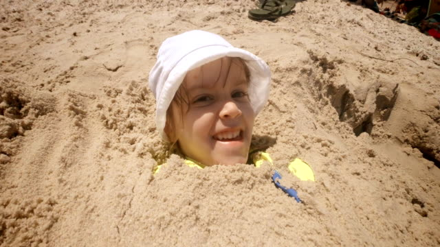 little girl playing in the sand buried up to her head - buried stock videos & royalty-free footage