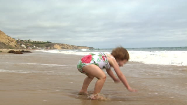 vídeos de stock e filmes b-roll de little girl playing in the surf - 18 a 23 meses