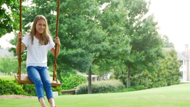 vidéos et rushes de petite fille jouant sur la balançoire dans le parc. - balançoire