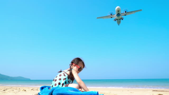 Little girl playing on the Beach with airplane landing