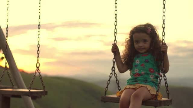 vídeos de stock, filmes e b-roll de menina brincando no balanço na luz de trás - cabelo encaracolado