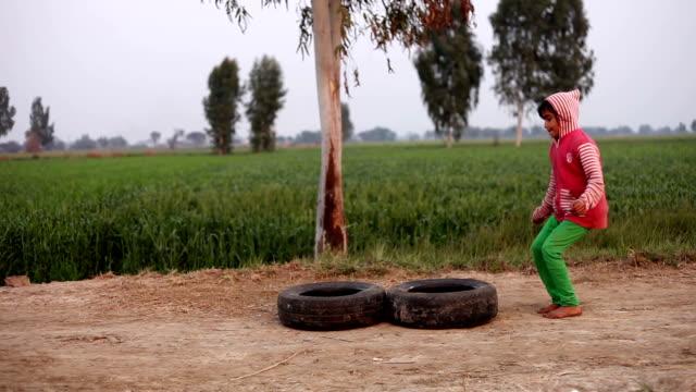 stockvideo's en b-roll-footage met meisje buiten spelen in de natuur - rubber