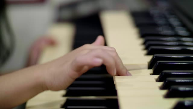 CU : Little girl (4-5 years) playing piano