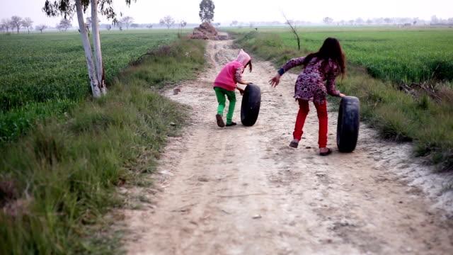 kleine mädchen spielen & läuft auf landstraße mit reifen - entwicklungsland stock-videos und b-roll-filmmaterial