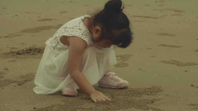 little girl playing sand - back lit stock videos & royalty-free footage