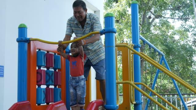 Kleine Mädchen spielen Schieberegler im Park mit Großvater