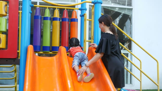 Kleine Mädchen spielen Schieberegler im Park mit Mutter