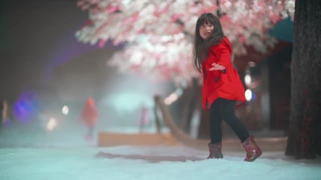 桜の木の背景と雪を再生する少女 - 恋に落ちる点の映像素材/bロール