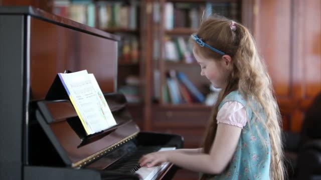 vidéos et rushes de petite fille jouant au piano - instrument de musique