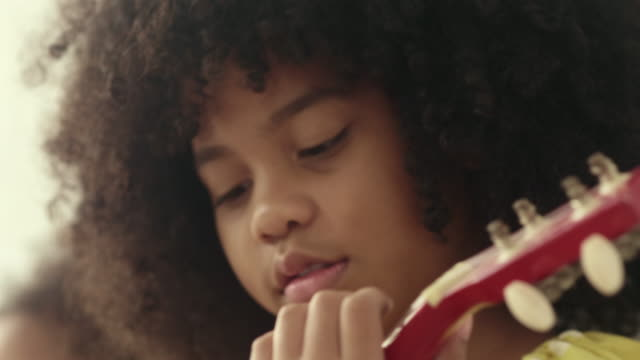 little girl playing ukulele and singing - afro stock videos & royalty-free footage