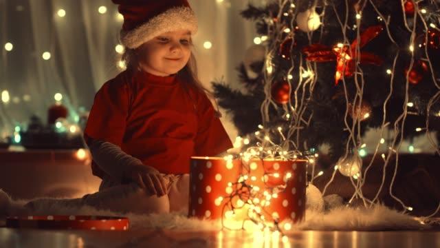 vidéos et rushes de petite fille jouant avec une boîte rougeoyante de cadeau sous un arbre de noel - cadeau de noël