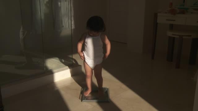 little girl playing with digital tablet. - 体重計点の映像素材/bロール