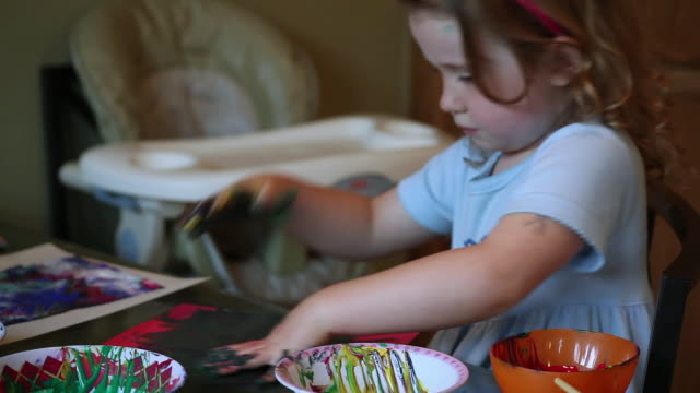 cu little girl playing with hand paints and showing her hands covered in paint / toronto, ontario, canada - kelly mason videos stock-videos und b-roll-filmmaterial