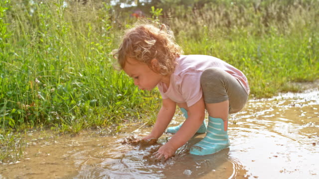 slo mo little girl playing with her hands in the muddy puddle - stivale video stock e b–roll