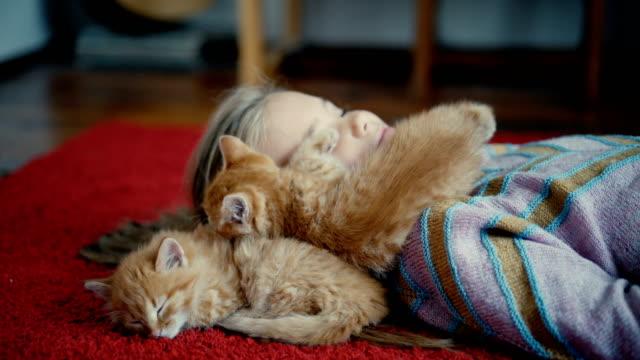 Kleines Mädchen mit Kätzchen drinnen spielen