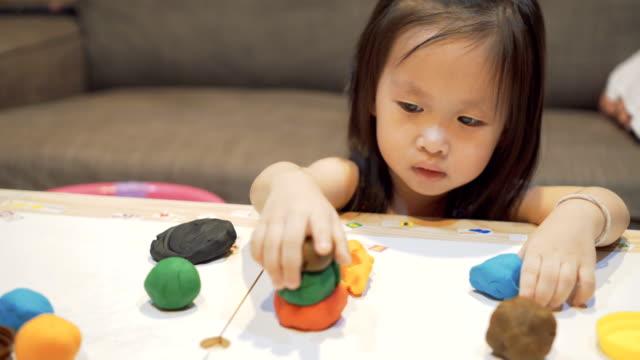 kleines mädchen spielt mit model-tonerde - lehm mineral stock-videos und b-roll-filmmaterial