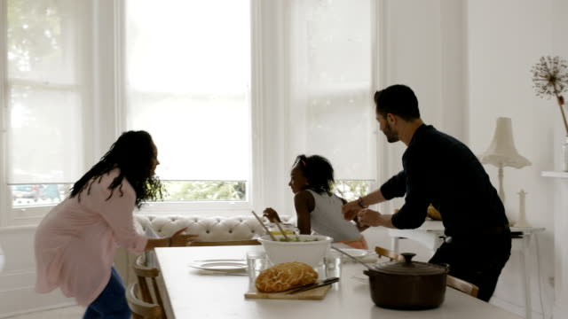 Little girl playing with parents in kitchen