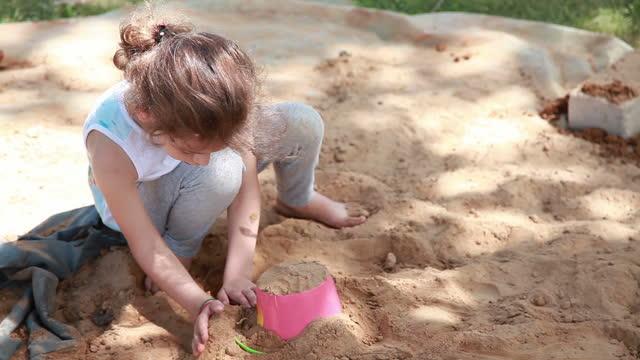 vidéos et rushes de petite fille jouant avec le sable dans l'arrière-cour - aire de jeux