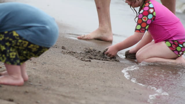 ms little girl playing with sand on beach at water break and little boy picking up stones on beach / toronto, ontario, canada - kelly mason videos stock videos & royalty-free footage