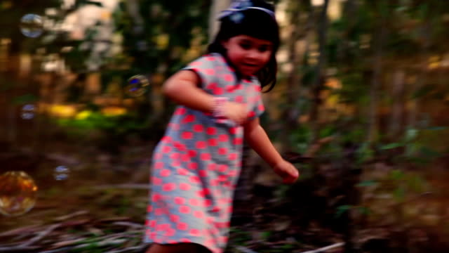 Little girl playing with soap bubbles in sunbeamed forest