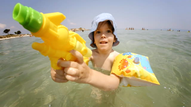 little girl playing with squirt gun and spraying water at camera - squirt gun stock videos and b-roll footage