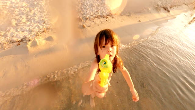 Little Girl Playing with Squirt Gun and Spraying Water at Camera