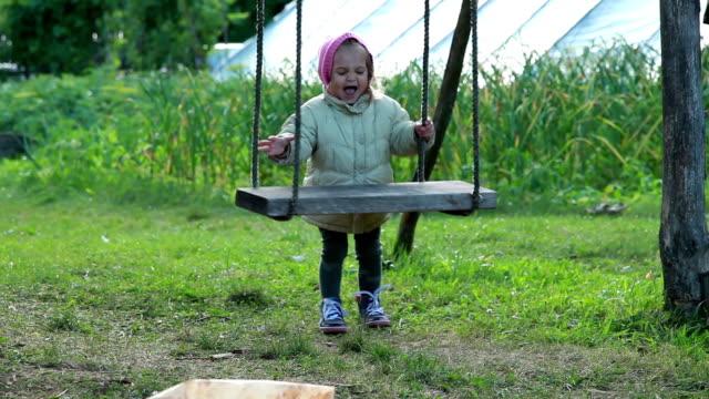 vidéos et rushes de petite fille jouant avec des oscillations dans l'arrière-cour - frapper activité physique