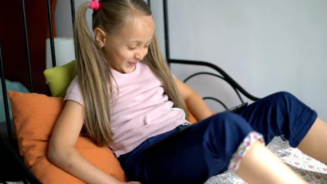 kleines mädchen mit dem digitalen tablet zu hause spielen. - 6 7 jahre stock-videos und b-roll-filmmaterial