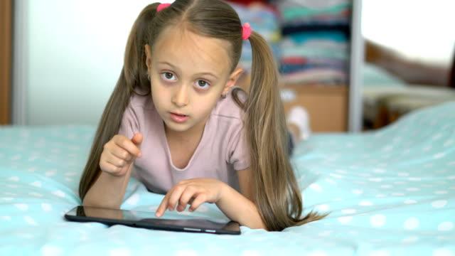 Kleine Mädchen spielen mit dem digitalen Tablet zu Hause