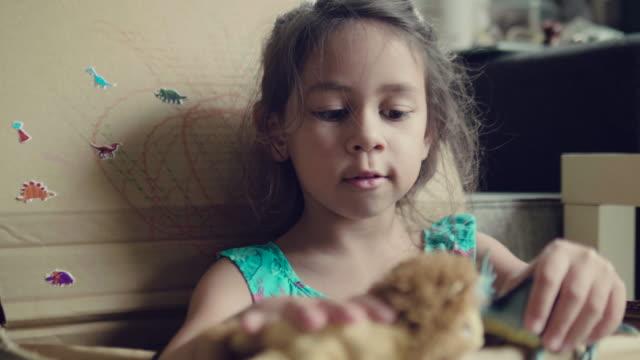 stockvideo's en b-roll-footage met een klein meisje, spelen met speelgoed dieren thuis - karton