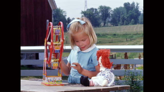 vídeos de stock e filmes b-roll de ms little girl playing with toys outdoors, farmland behind her / united states - dente humano