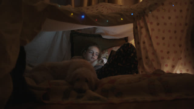 little girl plays on her tablet while inside her blanket fort. - reclining stock videos & royalty-free footage