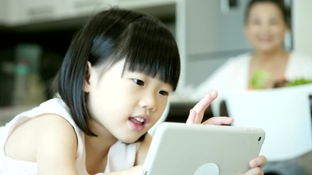 little girl plays video game on digital tablet - malaysian culture stock videos & royalty-free footage