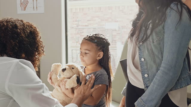 little girl plays with toy dog during well child medical appointment - pediatrician stock videos & royalty-free footage