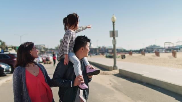 vídeos de stock e filmes b-roll de little girl pointing to the beach from father's shoulders - carregar uma pessoa nos ombros