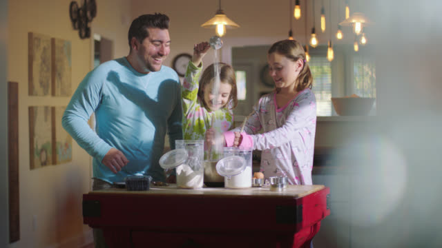 vidéos et rushes de ws. little girl pours flour into mixing bowl while sister stirs and dad laughs at breakfast time in family kitchen. - famille avec deux enfants