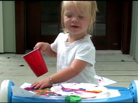 stockvideo's en b-roll-footage met little girl pours water on her painting - alleen meisjes