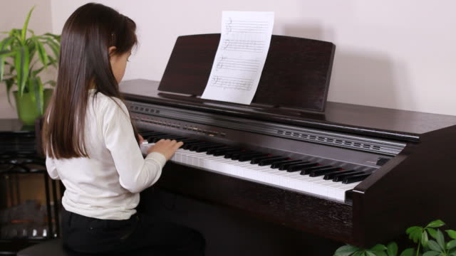 little girl practices piano - piano stock videos and b-roll footage
