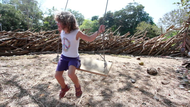 vídeos y material grabado en eventos de stock de ms little girl pushes herself on swing in natural playground / montezuma, nicoya peninsula, costa rica  - américa central