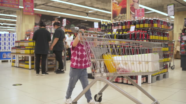 little girl pushing a shopping trolley in a supermarket - wide shot stock videos & royalty-free footage