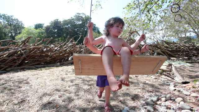 stockvideo's en b-roll-footage met ms little girl pushing little boy on swing outside in all natural playground / montezuma, nicoya peninsula, costa rica  - kelly mason videos